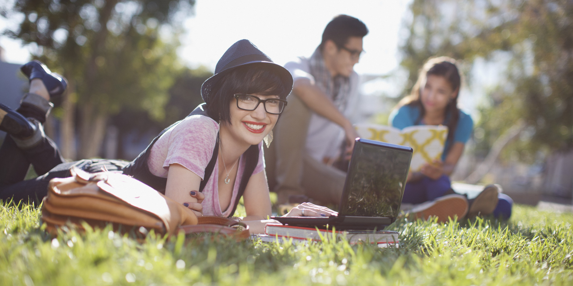 Student using laptop in grass